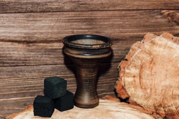 Een aardewerken kom voor een waterpijp met kokoskolen staat op een houten ondergrond.