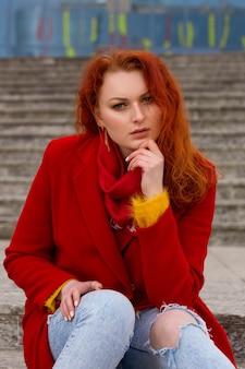 Een aardige jonge vrouw met rood haar in een rode jas en spijkerbroek zit buiten op de trap