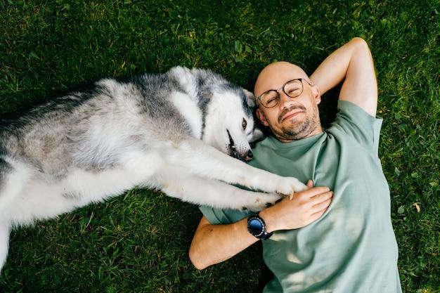 Een aardige man die met een hond op het gras ligt