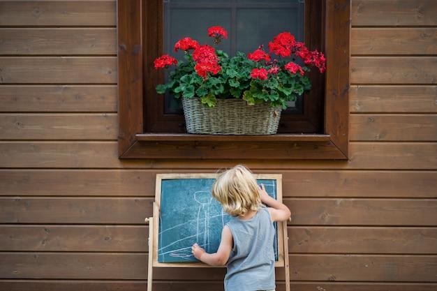 Een achteraanzicht van een gelukkige kleine blonde jongen die in de zomer buiten bij huis speelt.