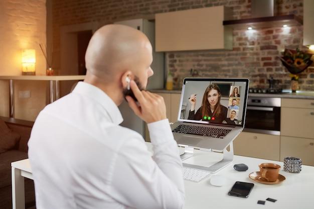Een achteraanzicht van een kale man die thuis op afstand op laptop werkt.