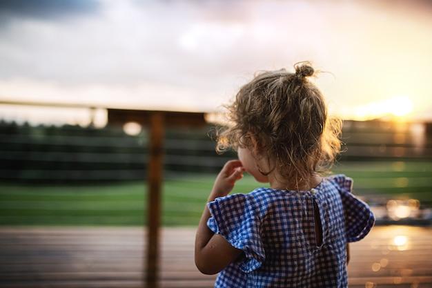 Een achteraanzicht van een klein meisje buiten in de schemering, vakantie in de natuur concept.