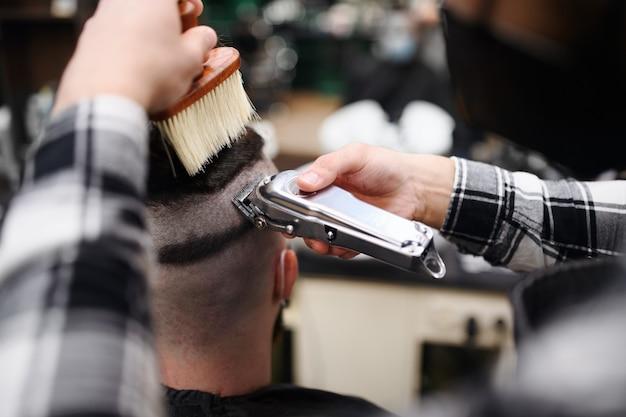 Een achteraanzicht van een man die een kapper bezoekt in een kapperszaak.