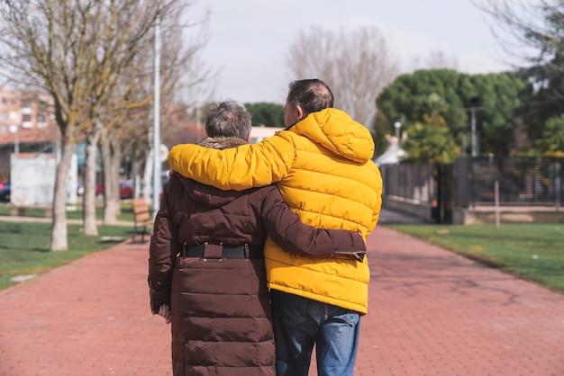 Een achteraanzicht van een mooie senior paar hand in hand buiten wandelen