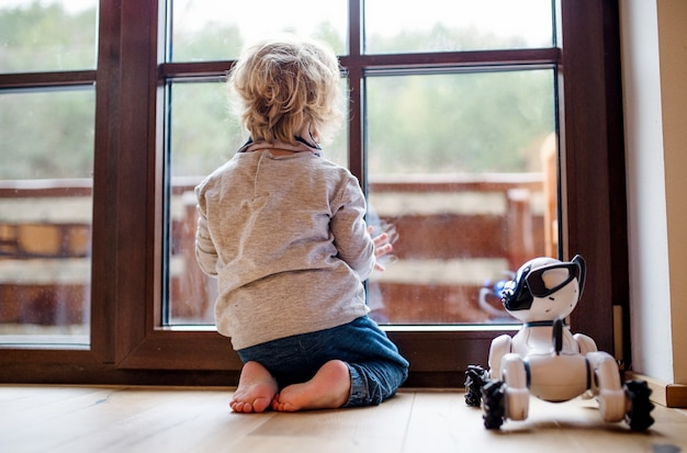 Een achteraanzicht van een schattige peuterjongen die binnenshuis op de vloer zit en met een robothond speelt.