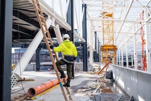 Een achteraanzicht van man werknemer buitenshuis op bouwplaats, werken.