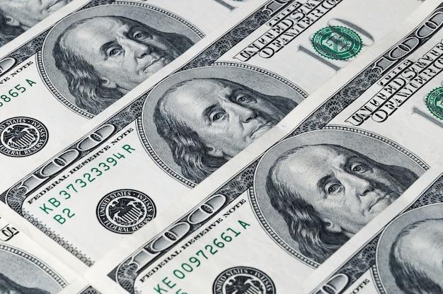 Een achtergrond van honderd dollarsrekeningen schikte diagonaal in een rij.