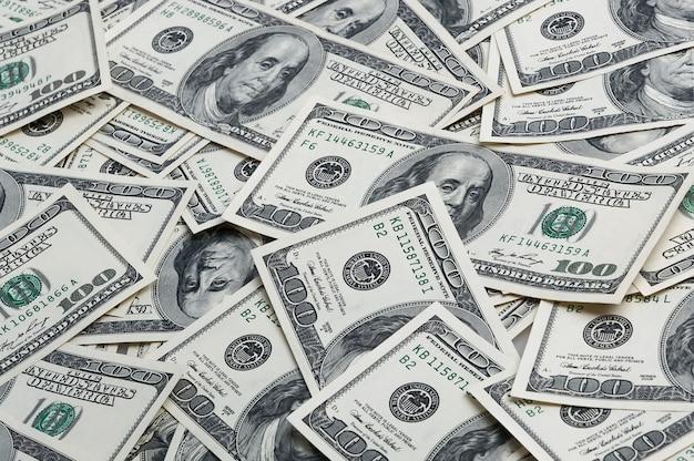 Een achtergrond van verspreide honderd dollarsrekeningen. uitzicht van boven.