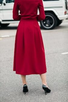 Een achterkant van een model poseert voor de camera in een prachtige rode jurk gemaakt van dichte stof met nette tailoring en witte knopen