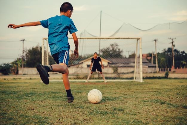 Een actiesportbeeld van een groep jonge geitjes die voetbalvoetbal voor oefening spelen