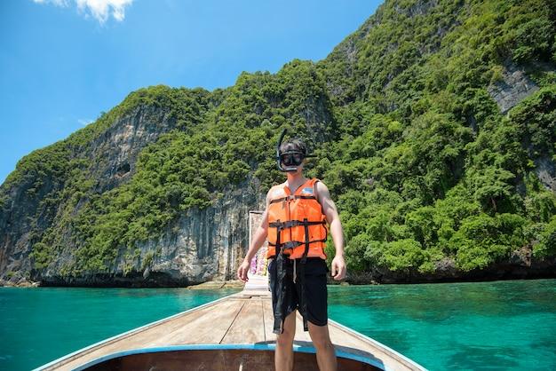 Een actieve man op thaise traditionele longtailboot is klaar om te snorkelen en te duiken, phi phi-eilanden, thailand