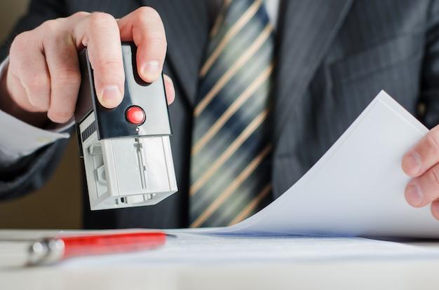 Een advocaat of notaris legt een zegel op het document. een stempel in de hand van een man.