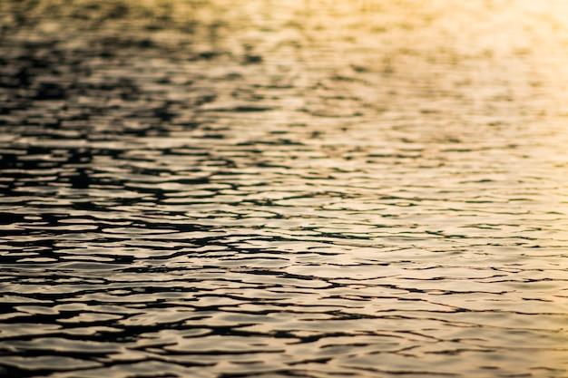 Een afbeelding op het water die de kleuren van de avondlucht weerspiegelt.