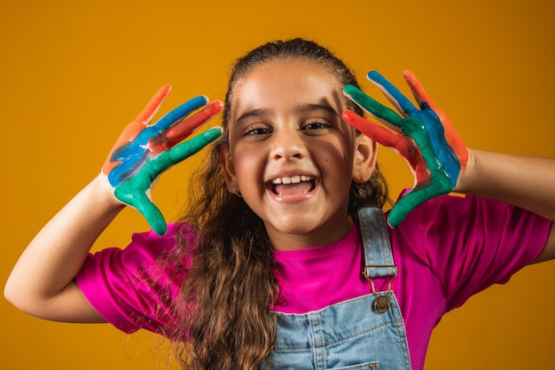Een afbeelding van een klein meisje met haar handen in de verf