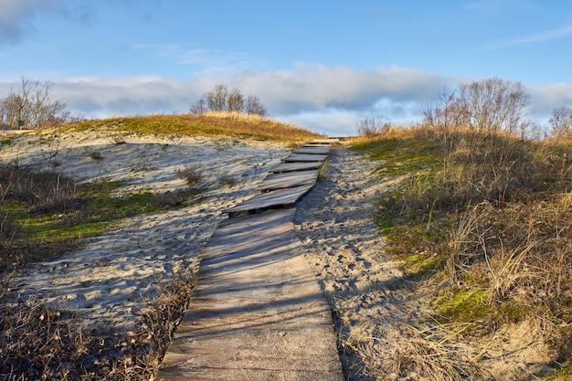 Een afbrokkelende houten promenade in de duinen bedekt met zand