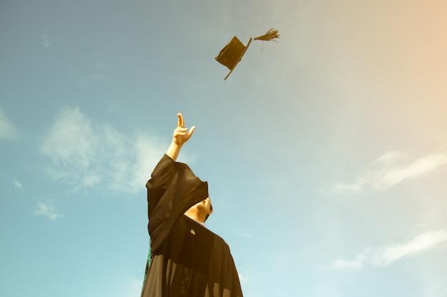 Een afgestudeerde gooide een hoed tot aan de hemel van de diploma-uitreiking in de graduation day