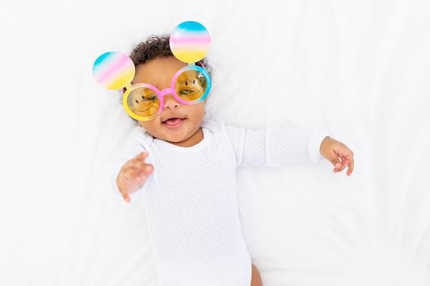 Een afrikaans-amerikaans klein kind met een grappige bril ligt op een wit bed en glimlacht