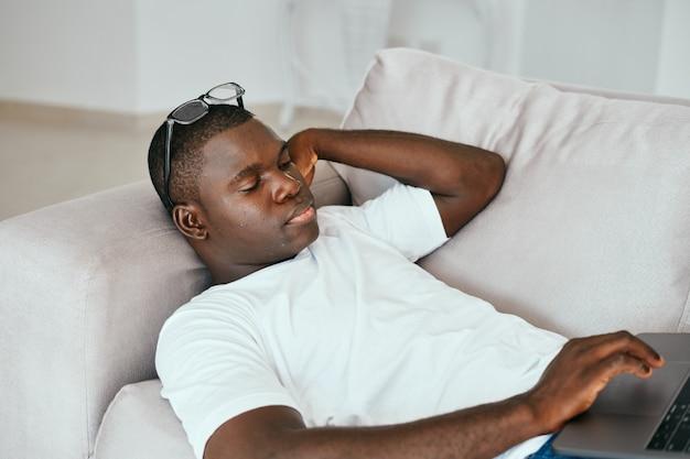 Een afrikaans uitziende man die in het weekend op de bank ligt