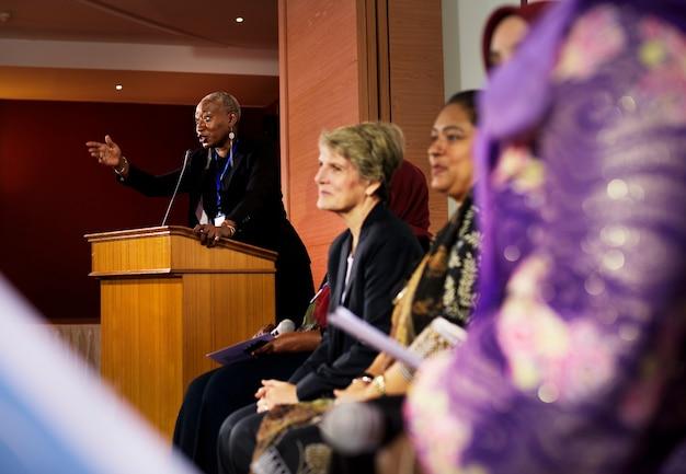 Een afrikaanse afdalingsman spreekt in een podium in een zaal vol internationale afgevaardigden
