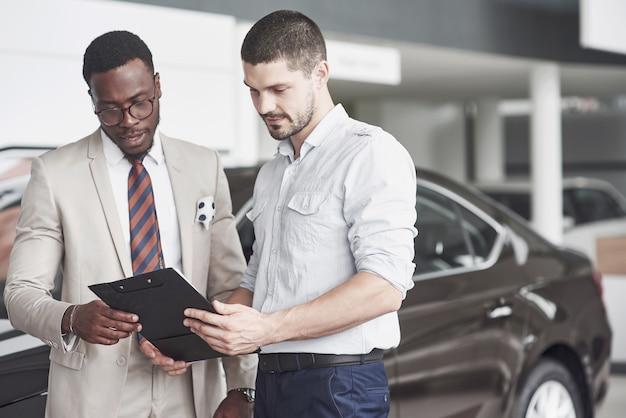 Een afrikaanse amerikaan met een adviseur bij een autodealer kiest een auto.