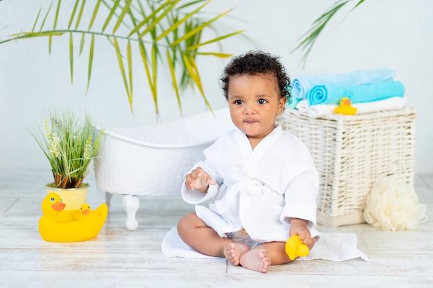 Een afrikaanse baby in een witte jas na een bad en bad speelt met een eend thuis, het concept van zorg en hygiëne van jonge kinderen.