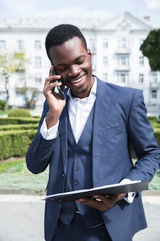 Een afrikaanse jonge zakenman die klembord bekijkt die op mobiele telefoon spreekt