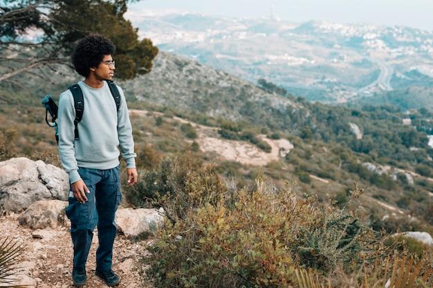 Een afrikaanse jongeman met uitzicht op de berg