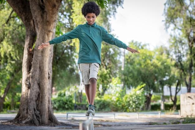 Een afrikaanse jongen met krullend haar stond met zijn armen uitgestrekt op de ijzeren reling