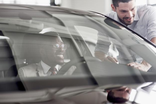 Een afrikaanse man die een nieuwe auto koopt, controleert een auto in gesprek met een professionele verkoper.