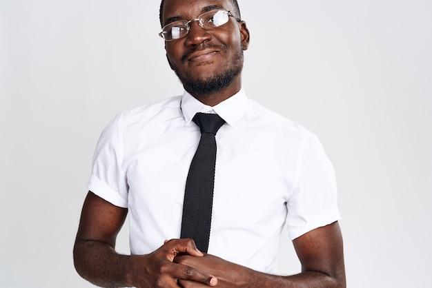 Een afrikaanse man in een overhemd en stropdas op een lichte gebaren met zijn handen