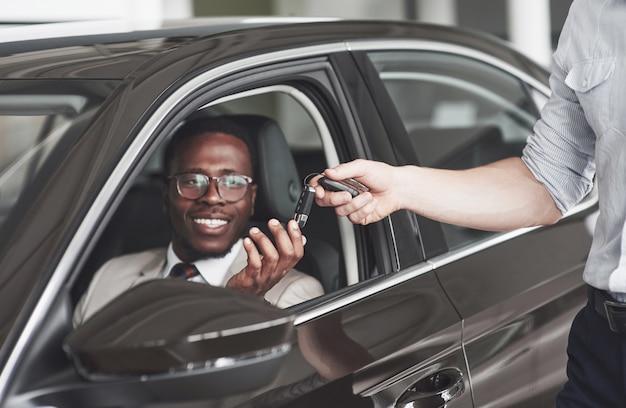 Een afro-amerikaan krijgt bij een autodealer sleutels van een auto.