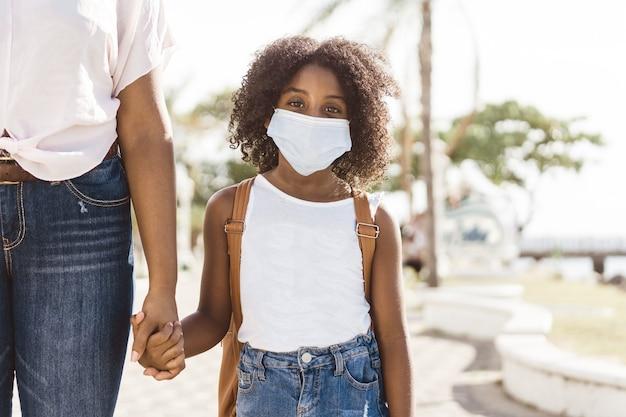 Een afro-amerikaans meisje met een rugzak die een masker draagt, terug naar schoolconcept
