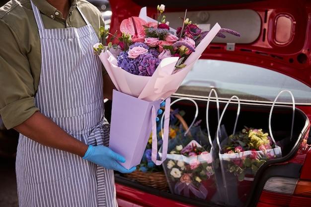 Een afro-amerikaans persoon die een rode kofferbak vult met de zakken bloemen