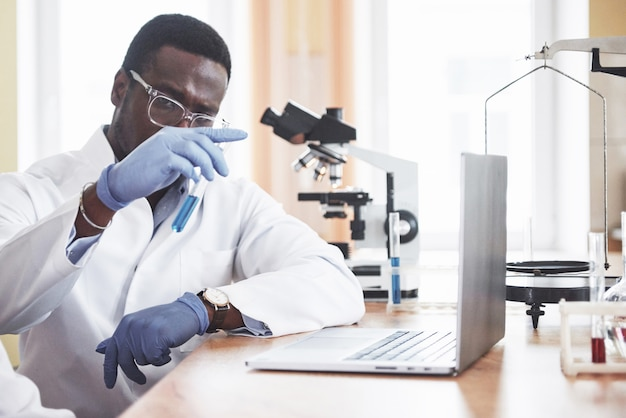 Een afro-amerikaanse arbeider werkt in een laboratorium om experimenten uit te voeren.