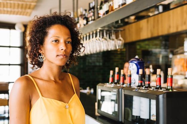 Een afro-amerikaanse jonge vrouw aan toog