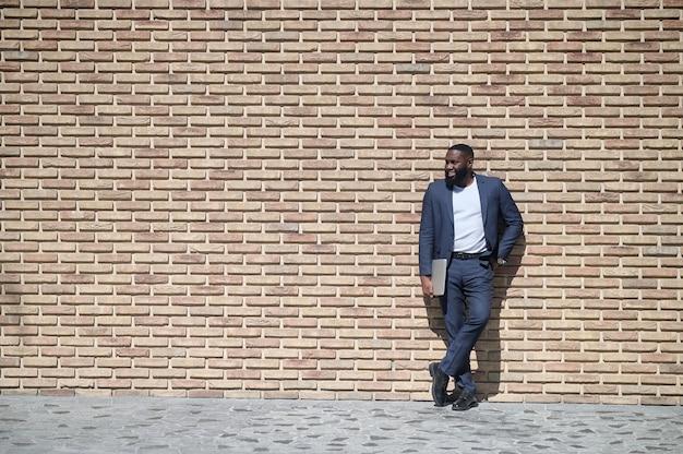 Een afro-amerikaanse man in een pak die bij de bakstenen muur staat