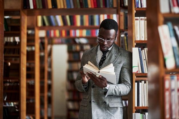 Een afro-amerikaanse man in een pak staande in een bibliotheek in de leeszaal.
