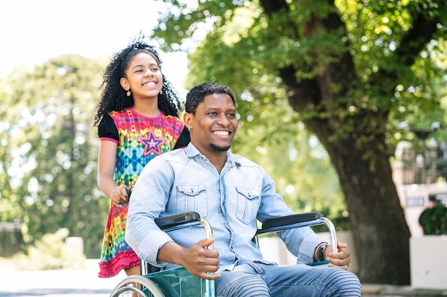 Een afro-amerikaanse man in een rolstoel genieten van een wandeling buiten met zijn dochter