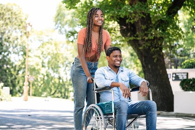 Een afro-amerikaanse man in een rolstoel genieten van een wandeling buiten met zijn vriendin.