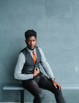 Een afro-amerikaanse man met een vest die op een bank zit en modellenwerk doet