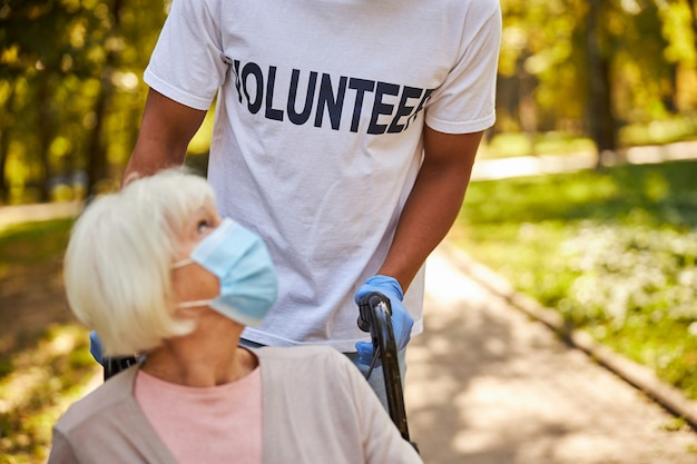 Een afro-amerikaanse vrijwilliger die medische handschoenen draagt en de handvatten van een rolstoel vasthoudt met een ouder wordende vrouw