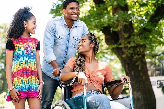 Een afro-amerikaanse vrouw in een rolstoel die geniet van een wandeling buiten met haar dochter en echtgenoot.