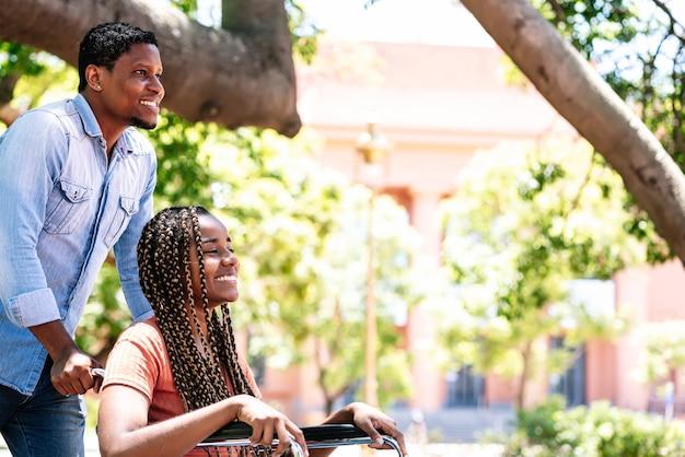 Een afro-amerikaanse vrouw in een rolstoel die geniet van een wandeling in het park met haar vriendje