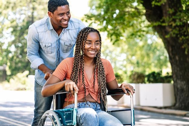 Een afro-amerikaanse vrouw in een rolstoel die geniet van een wandeling met haar vriendje.