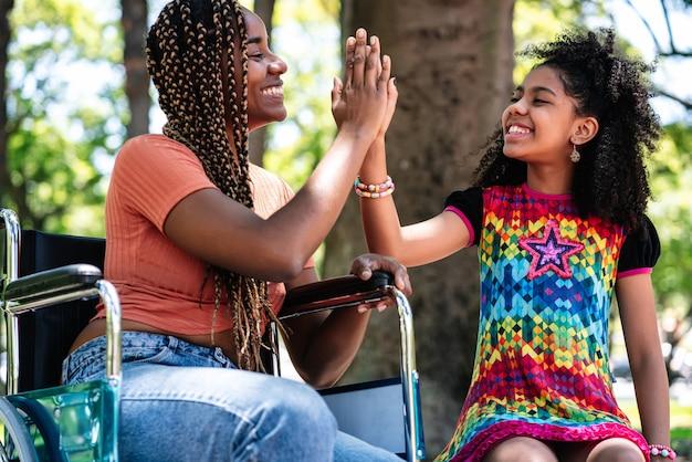 Een afro-amerikaanse vrouw in een rolstoel geniet van een dag in het park en heeft plezier met haar dochter