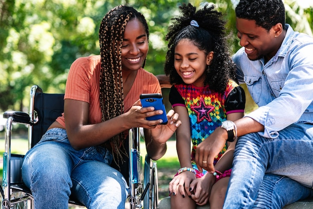 Een afro-amerikaanse vrouw in een rolstoel geniet van een dag in het park met haar gezin terwijl ze samen een mobiele telefoon gebruikt
