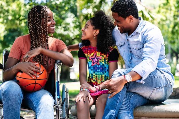 Een afro-amerikaanse vrouw in een rolstoel geniet van een dag in het park met haar gezin.