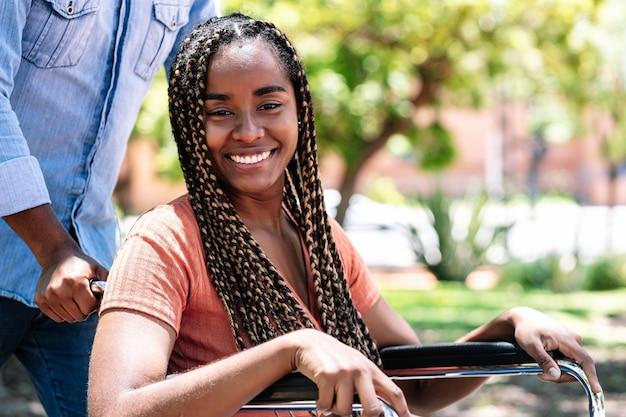 Een afro-amerikaanse vrouw in een rolstoel geniet van een wandeling in het park met haar vriendje.