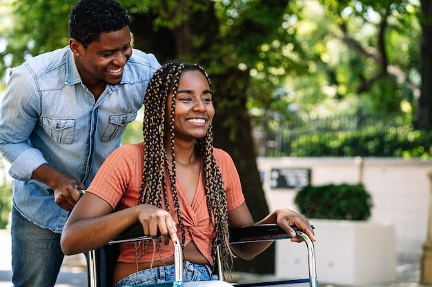 Een afro-amerikaanse vrouw in een rolstoel geniet van een wandeling met haar vriend buiten op straat