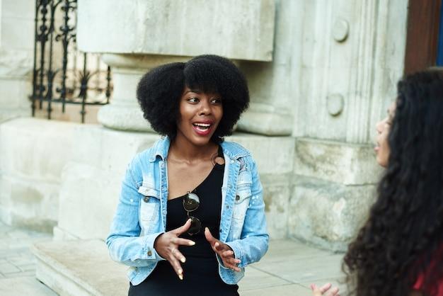 Een afro-amerikaanse vrouw vertelt emotioneel een verhaal aan haar vriend. stedelijke achtergrond. multi-etnische groep.